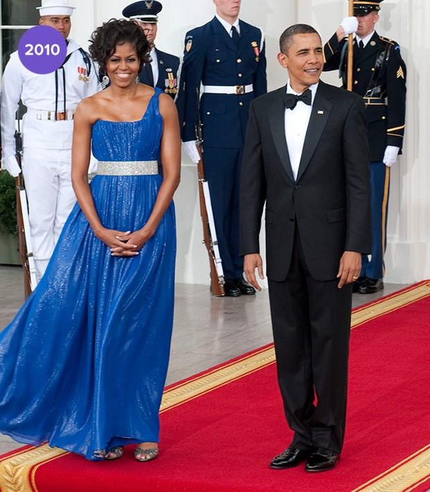 Em 2010: Michelle Obama apostou em longo azul royal com decote de um ombro só e cintura marcada em prata de Peter Soronen (Foto: Getty Images)